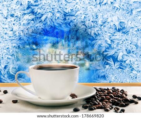 hot coffee near frozen winter window - stock photo