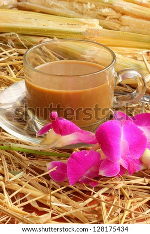 Hot coffee on the floor with straw and sugarcane Cruz Orchid - stock photo