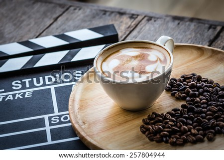 hot coffee on the table with coffee bean and film sign - stock photo