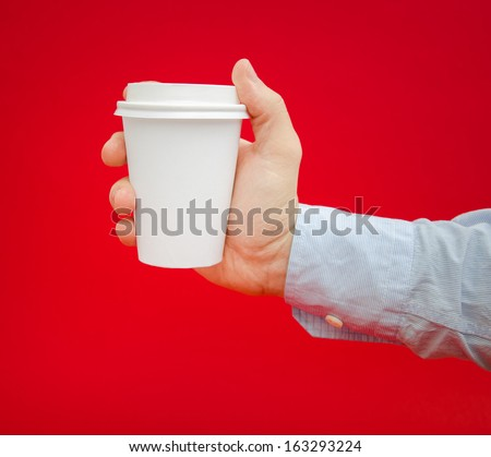 Hot coffee to go being held by a business man over a red alerted dangerous background - stock photo