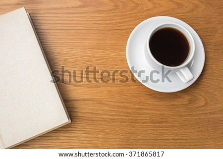 Hot coffee, top view of a blank notebook and a cup of coffee on a wooden table