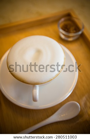 Hot coffee with a white ceramic cup, disk, spoon on a wood tray