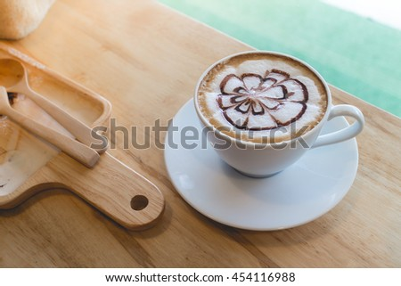 hot coffee with foam milk art in afternoon break. Coffee mocha on the wood desk.(selective focus, vintage effect) - stock photo