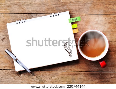 Hot coffee with idea paper note on wood background. - stock photo