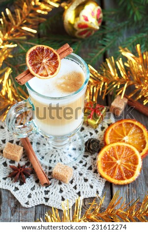 Hot coffee with milk in a glass on a wooden table with pieces of sugar, cinnamon sticks, candied orange slice and yellow tree toys. Selective focus, toned - stock photo