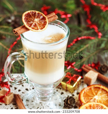 Hot coffee with milk in a glass on a wooden table with pieces of sugar, cinnamon sticks, candied orange slice and red tree toys. Selective focus, toned - stock photo