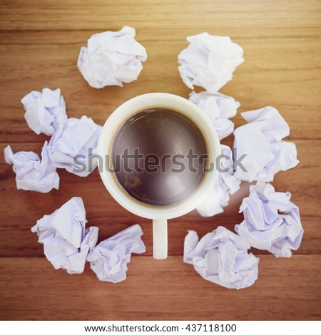 Hot coffee with trash and crumple paper, business concept in finding idea. Wood desk background in vintage style. - stock photo