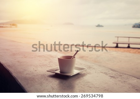 Hot coffee with tropical beach. Vintage filter. - stock photo