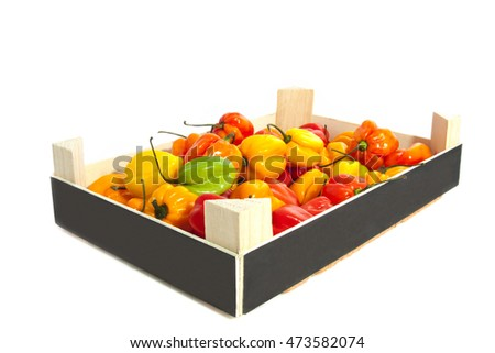 Hot colorful chili peppers in a wooden crate over white