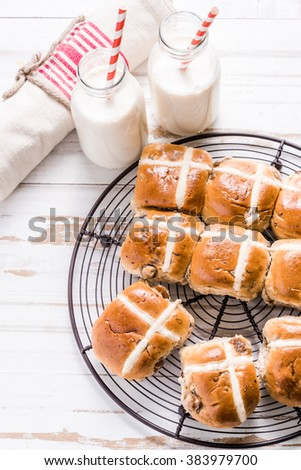 Hot cross bun on tray with Easter vibrant eggs and milk. Easter breakfast concept, view from overhead. - stock photo