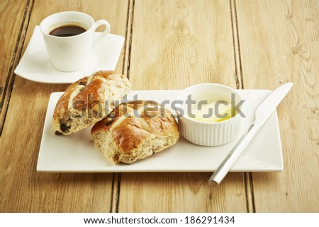 Hot cross bun on white dish and wooden table top - stock photo
