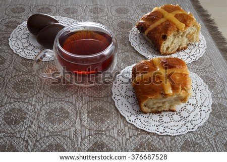 Hot cross buns, cup of tea and chocolate eggs on easter breakfast table, horizontal view - stock photo