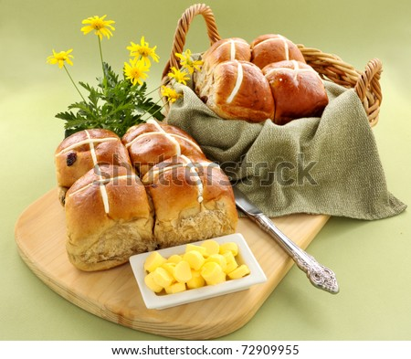Hot cross buns in a basket and some with butter and daisies. - stock photo