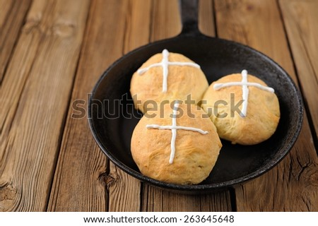 Hot cross buns in cast iron skillet on wooden background - stock photo