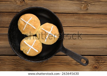 Hot cross buns in cast iron skillet on wooden background with space - stock photo