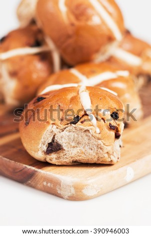 Hot cross buns on a timber board with a white background.