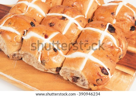 Hot cross buns on a timber board with a white background. - stock photo
