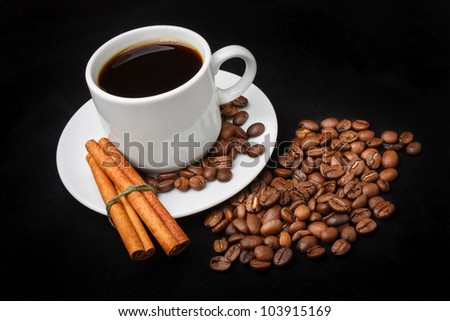 Hot Cup of Coffee, Roasted Coffee Beans, Cinnamon Sticks on Black Velvet Background