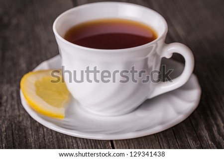 Hot cup of tea in white mug with lemon. Standing on wooden table. - stock photo