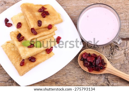 Hot delicious pancakes. Thin pancakes with berries. Cranberry. Dried berries. Yogurt and pancakes. Fried pancakes. The food on the table. Cup of yogurt, crepes and dried cranberries. Sweet pancakes. - stock photo