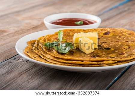 Hot delicious paratha with ghee and tomato sauce - stock photo