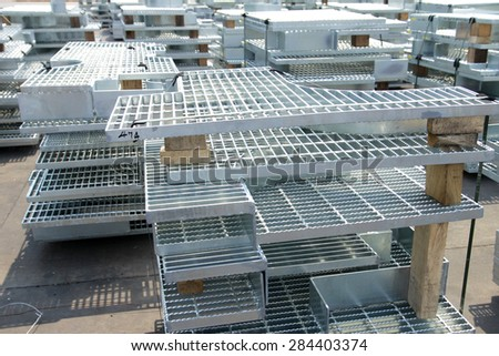 Hot-dip galvanized steel grating bunch in warehouse before shipment - stock photo