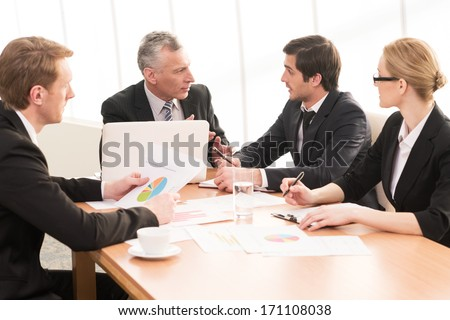 Hot discussion. Four business people in formalwear discussing something while sitting together at the meeting - stock photo