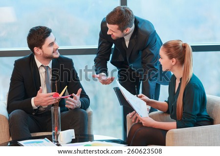 Hot discussion. Group of business people in formalwear discussing something while sitting together at the meeting - stock photo
