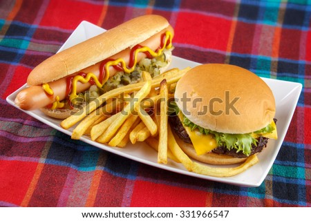 Hot dog , french fries and cheese burger on plate , fast food lunch on red fabric surface