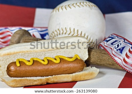hot dog on bun with baseball and bat on American flag - stock photo