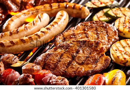 Hot dog sausages, beef steak, chicken patties and vegetables on hot flaming grill - stock photo