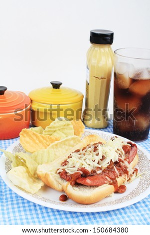 Hot dog sliced and fried on bun and covered with chili and grated Pepper Jack Cheese.  Served with veggie chips and ice cold soft drink. - stock photo