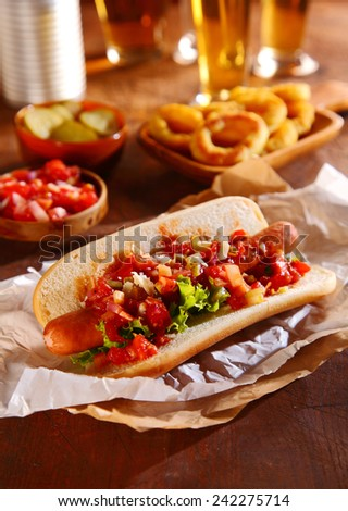Hot dog topped with spicy fresh vegetable relish with tomato, onion, chili, and lettuce on a smoked Wiener sausage in a fresh hotdog roll served in a pub or bar with beer and squid - stock photo