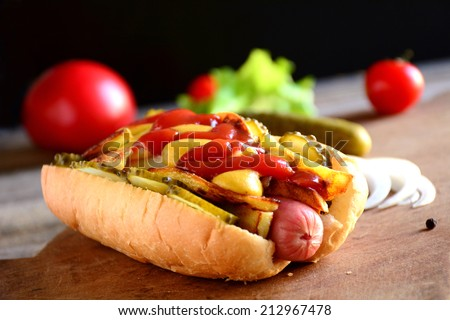 Hot dog with juicy sausage, fried potatoes, pickles, spicy mustard and sweet ketchup sauce on wooden cutting board, black background. Close up, fast food image - stock photo