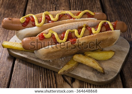 Hot Dog with ketchup and mustard (close-up shot) on wooden background - stock photo