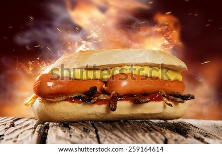 Hot dog with mustard and ketchup on wooden table. - stock photo