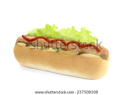 Hot dog with pickle, lettuce leaf, sausage and ketchup - stock photo