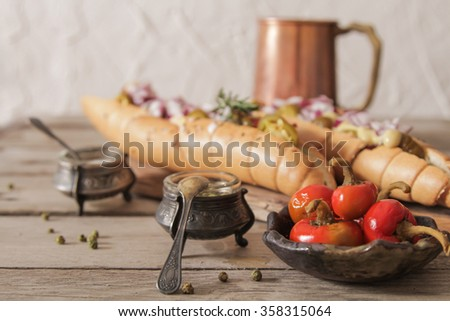 Hot dog with sausage and beer and red hot pepper on a brown background propki - stock photo