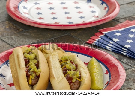 Hot dogs at a July 4th cookout are dressed with ketchup, mustard and relish and are served with potato chips and a pickle.  Selective focus was used on this image which is one in a patriotic series. - stock photo