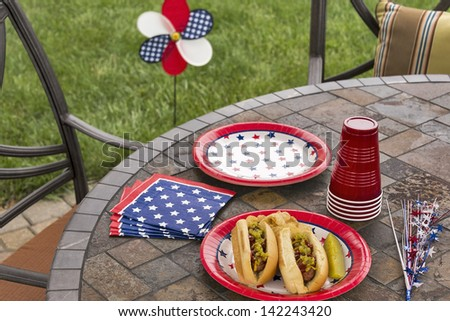 Hot dogs at a July 4th cookout are dressed with ketchup, mustard and relish and are served with potato chips and a pickle.  This image is in one in a series of patriotically themed images. - stock photo