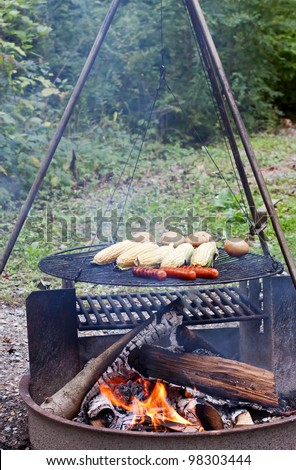 Hot dogs,corn and potatoes cooking on a grill at a Pennsylvania State Park. - stock photo