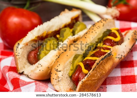 Hot dogs on a red checkered napkin with tomato and onion