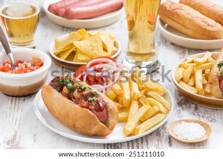 hot dogs with French fries, beer and snacks, horizontal - stock photo