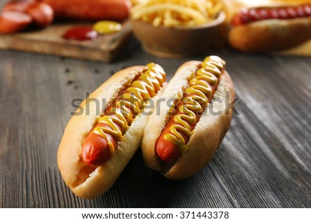 Hot dogs with fried potatoes and fresh sausages on wooden background - stock photo