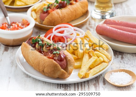 hot dogs with tomatoes, onions and french fries, close-up - stock photo