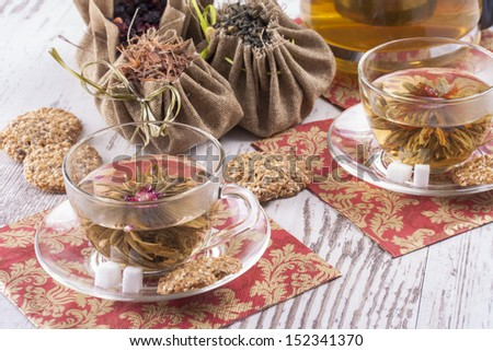 Hot drink - a green tea in a glass cup on bright wooden background.