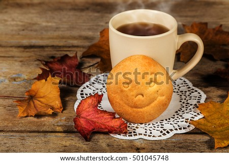 Hot drink and biscuit with a smile and autumn leaves on a wooden table surface