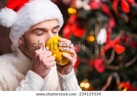 Hot drink at winter night. Handsome young man in Santa hat drinking hot drink with Christmas Tree in the background  - stock photo