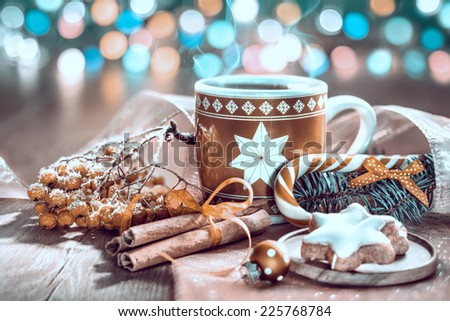 Hot drink, Christmas cookies and candy cane on decorated table, toned image - stock photo