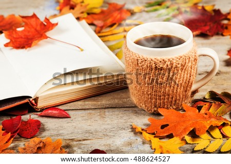 Hot drink in a large cup, book, colorful autumn leaves